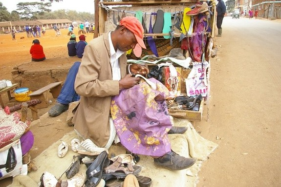 A man repairs shoes along the streets of the Thika Super Highway in Nairobi, capital of Kenya, July 23, 2015. [Photo/Xinhua]